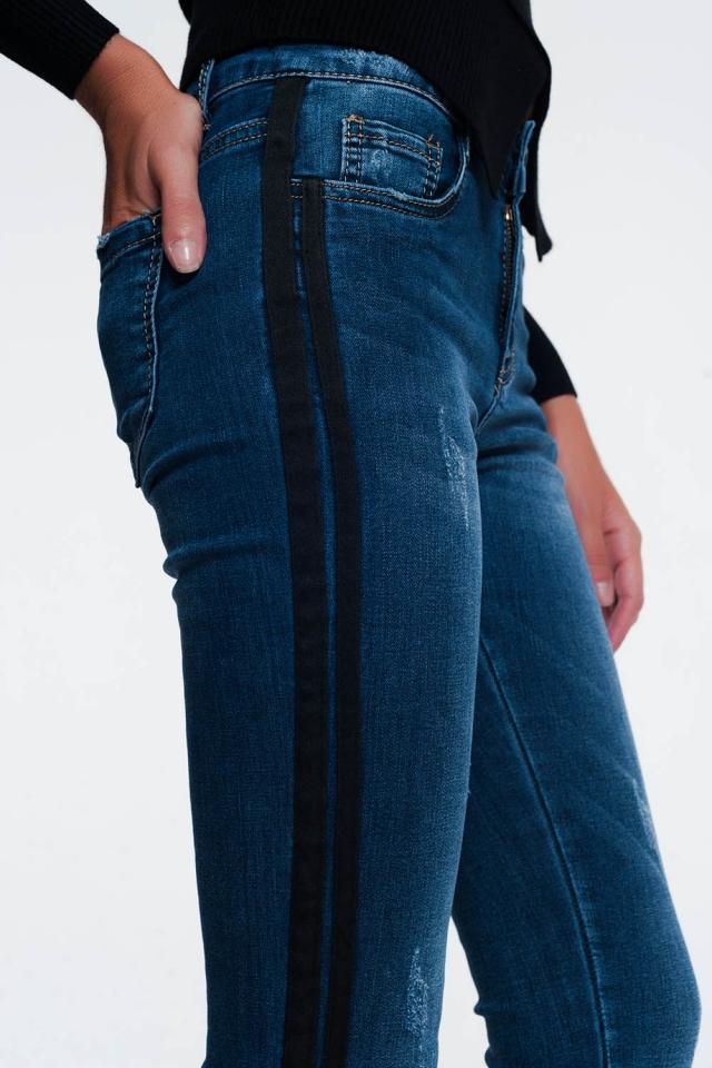 Aansuitende jeans met slijtage en streep aan de zijkant