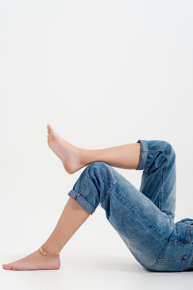 Ruimvallende jeans met scheur in middenblauw